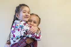 Two little girls sisters hugging. The manifestation of sisters& x27; love and friendship.  Stock Image