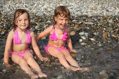 Two little girls sit ashore in water. Two little girls in pink sit ashore in water Royalty Free Stock Photos