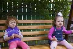 Two little girls are sitting on a hanging bench and eating cookies royalty free stock images