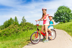 Two little girls sit on a bicycle Royalty Free Stock Images