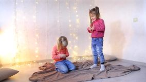 Two little girls sit on floor and play. Two young girls of European appearance sit on floor in living room and play, one child offended and sits angry stock footage