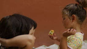 Two little girls sit outside and eat apples. girlfriends talk. stock footage