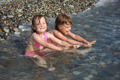 Two little girls sit  in sea Stock Photography