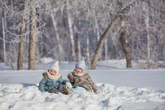 Two little girls sit in snowdrift and fool in winter Royalty Free Stock Photos