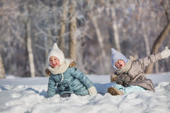 Two little girls sit in snowdrift and make faces in winter Stock Photos