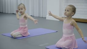 Two little girls sit on their laps and do dance exercises on training. Talented and cute children are diligently engaged in studio for development of stock video