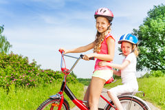 Two little girls sitting on a bicycle outdoors Royalty Free Stock Images