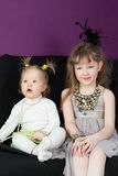 Two little girls sitting on the black sofa. In fashionable clothes royalty free stock photography