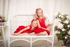 Two little girls sitting in a chair Stock Photos