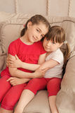 Two little girls sitting in a chair Stock Photo
