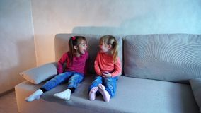 Two little girls sitting on couch and playing, showing each other tongues. Two sisters from American family sit on sofa in living room, show each other tongues stock video