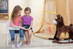 Two little girls are sitting in the game room. On the chairs and read a book stock photos