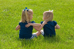 Two Little girls sitting in grass Royalty Free Stock Photography