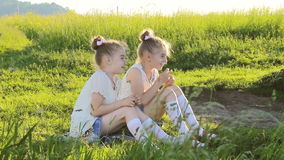 Two little girls sitting on grass talking have fun. HD stock video