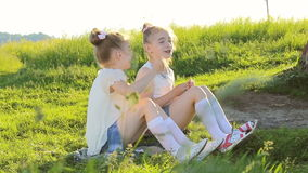 Two little girls sitting on grass talking have fun stock video