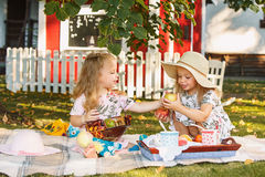 Two little girls sitting on green grass royalty free stock photos