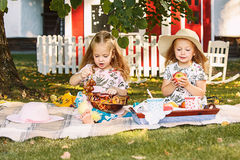 Two little girls sitting on green grass stock photos