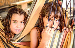 Two little girls sitting in the hammock on the beach Royalty Free Stock Photos