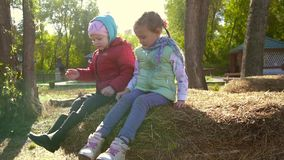 Two little girls sitting on a haystack and throwing hay down. Slow motion stock video footage