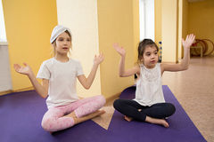 Two little girls sitting in lotus posture in gym Stock Photos