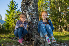 Two little girls sitting near the birches in the forest. Walking. Royalty Free Stock Photo