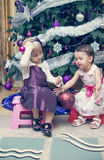 Two little girls sitting near the Cristmas tree Stock Photos