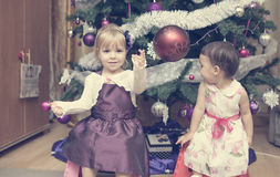 Two little girls sitting near the Cristmas tree Royalty Free Stock Images