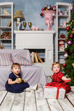 The two little girls sitting at studio with christmas decorations Royalty Free Stock Photo