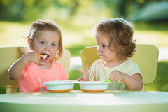 Two little girls sitting at a table and eating together against green lawn Stock Image
