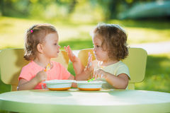 Two little girls sitting at a table and eating together against green lawn Stock Photo
