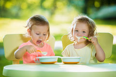 Two little girls sitting at a table and eating together against green lawn Royalty Free Stock Images
