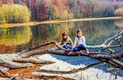 Two little girls sitting on the tree on Lake Biogad (Biogradsko Royalty Free Stock Photos