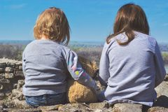 Two little girls sitting and watching sky. On a sunny day Royalty Free Stock Photos
