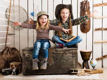 Two little girls sitting on wooden chest with hands up Stock Images