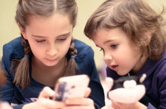 Two little girls with smartphone lying on bed at home stock image