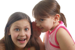 Two little girls speaking about something. (isolated over white background Royalty Free Stock Photos