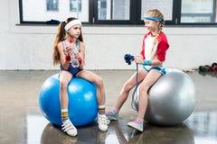 Two little girls in sportswear sitting at fitness studio. Children sport concept Stock Photo