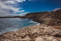 Two little girls stand on beautiful sea shore in Cyprus. A view of a sea shore in Kavo Greko nenar Aiya Napa, Cyprus royalty free stock photography