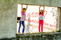 Two little girls  standing on the old window opening. Two little girls are standing on the old window opening Stock Images
