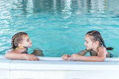 Two little girls swim in the pool. Two friends in the pool.Children playing in pool. Two little girls having fun in the pool royalty free stock photo