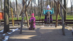 Two little girls on swing ride - horses. Two little girls in the late autumn ride on wooden chain swing - horses, against the background of city park stock video footage