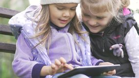 Two little girls with tablet computer sits on the bench in garden. Two little girls with black tablet computer sits on the bench in garden. Medium close up stock footage