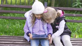 Two little girls with tablet computer sits on the bench in garden. Two little girls with black tablet computer sits on the bench in garden. Medium long shot stock video footage