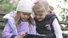 Two little girls with tablet computer sits on the bench in garden. Two little girls with black tablet computer sits on the bench in garden. Medium shot stock video