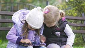 Two little girls with tablet computer sits on the bench in garden. Two little girls with black tablet computer sits on the bench in garden. Medium shot stock footage