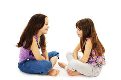 Two little girls talking. Isolated on white background stock photography