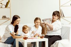 Little girls, attractive young mother and charming grandmother are sitting at home royalty free stock photo