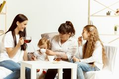 Little girls, attractive young mother and charming grandmother are sitting at home royalty free stock images