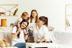 Little girls, attractive young mother and charming grandmother are sitting at home royalty free stock photography