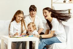 Little girls, attractive young mother and charming grandmother are sitting at home stock photos